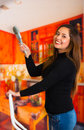 Beautiful happy young woman painting using brush