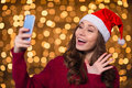 Beautiful happy young woman in santa claus hat using smartphone Royalty Free Stock Photo