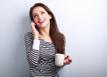 Beautiful happy young woman talking on mobile phone and drinking Royalty Free Stock Photo
