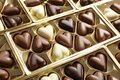 Beautiful heart shaped chocolate candies in box as background Royalty Free Stock Photo