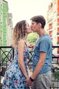 Beautiful heterosexual couple kisses on the balcony. Multicolored urban houses on the background.