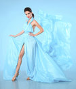 Beautiful High fashion woman in blue dress posing in studio. Glamour model in blowing chiffon dress. Stunning Woman Royalty Free Stock Photo