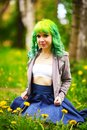 Beautiful hipster alternative young woman with yellow hair sits in grass with dandelion in park Royalty Free Stock Photo