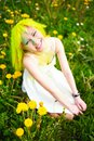 Beautiful hipster alternative young woman with yellow hair sits in grass with dandelion in park green Royalty Free Stock Image