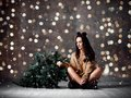 Beautiful hipster woman with Christmas fir tree and lights in knitted sweater blouse Royalty Free Stock Photo