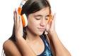 Beautiful hispanic teenage girl enjoying music on bright orange headphones isolated white Royalty Free Stock Photo