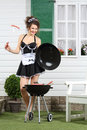 Beautiful housemaid keeps lid and sausage on fork near barbecue country house Royalty Free Stock Photos