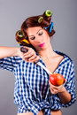Beautiful housewife with curlers holding apple and the knife portrait of Royalty Free Stock Images