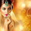 Beautiful indian girl portrait hindu woman with menhdi tattoo perfect make up and accessories hiding her face behind a veil bride Royalty Free Stock Photos