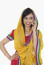 Beautiful indian woman in traditional wear answering phone call over white background Stock Images
