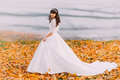 Beautiful innocent young brunette bride in gorgeous white dress stands on fallen leaves at riverside Royalty Free Stock Photo