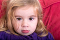 Beautiful innocent young girl close up facial portrait of a blond with a solemn wide eyed expression staring into the camera Royalty Free Stock Photos