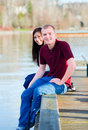 Beautiful interracial couple sitting on wooden dock over lake young dangling feet sides Stock Image
