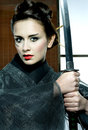 Beautiful japanese kimono woman with samurai sword grey in traditional room Stock Photography