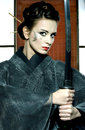 Beautiful japanese kimono woman with samurai sword grey in traditional room Stock Photo