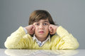 Beautiful kid with deep thoughts thinking against grey background Royalty Free Stock Photo