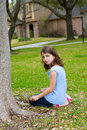 Beautiful kid girl smiling sitting on park lawn relaxed outdoor Stock Image