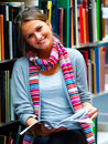 Beautiful lady holding book in library Royalty Free Stock Photo
