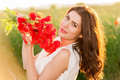 Beautiful lady over Sky and Sunset in the field holding a poppies bouquet, smiling Royalty Free Stock Photo