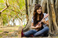 Beautiful lady playing ukulele under a tree Stock Photos