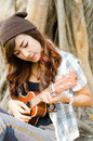 Beautiful lady playing ukulele under a tree Royalty Free Stock Photos