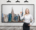 A beautiful lady is pointing out the picture of New York City on the wall. Wooden floor, concrete wall and three black ceiling lig Royalty Free Stock Photo