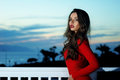 Beautiful lady portrait of young elegant in red dress against sunset sky Royalty Free Stock Photo