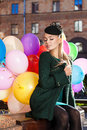 Beautiful lady in retro outfit holding a bunch of balloons in ci looking girl with closed eyes dark green coat and hat sits on Royalty Free Stock Photography