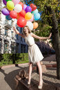 Beautiful lady in retro outfit holding a bunch of balloons in ci pretty woman with long legs white summer dress multicolored Royalty Free Stock Images
