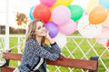 Beautiful lady in retro outfit holding a bunch of balloons in ci smiling blonde girl sits on park bench with multicolored Stock Photos