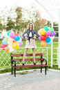 Beautiful lady in retro outfit holding a bunch of balloons in ci smiling blonde girl stands on park bench with multicolored Royalty Free Stock Image