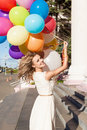 Beautiful lady in retro outfit holding a bunch of balloons on th portrait blonde girl with multicolored summer sunny day at stairs Royalty Free Stock Photography