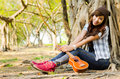 Beautiful lady sitting under the tree with ukulele Stock Image