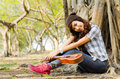 Beautiful lady sitting under the tree with ukulele Stock Photos