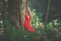 Beautiful lady in tropical forest young red dress Royalty Free Stock Photo