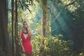 Beautiful lady in tropical forest young red dress Royalty Free Stock Photography