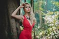 Beautiful lady in tropical forest young red dress Stock Photo