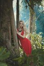 Beautiful lady in tropical forest young red dress Royalty Free Stock Images