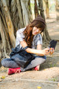 Beautiful lady useing smart phone under a tree Stock Photo