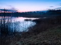 Beautiful lake near city with colorful sunset sky tranquil vibrant landscape over calm and of shore reeds useful as background Royalty Free Stock Photo