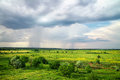 Beautiful landscape with cloudy rainy sky green fields and Royalty Free Stock Images