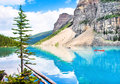 Beautiful landscape with rocky mountains and mountain lake in alberta canada tourists canoeing on azure Royalty Free Stock Image
