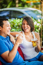 Beautiful latin couple in a restaurant an outdoors drinking beer Stock Image