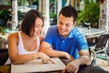 Beautiful latin couple in a restaurant an outdoors looking at the menu Royalty Free Stock Photos