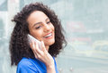 Beautiful latin woman with curly hair at phone in city Royalty Free Stock Photo