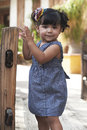 Beautiful latina girl hispanic toddler playing at rustic garden park on sunny day Royalty Free Stock Images