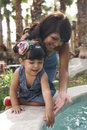 Beautiful latina mother and daughter hispanic playing together in garden on sunny day Royalty Free Stock Photo