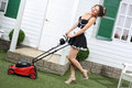 Beautiful laughing housemaid with lawn mower near door of country house Royalty Free Stock Images