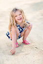 Beautiful laughing little girl with long blond hair squatting and drawing in the sand on the beach in summer day Royalty Free Stock Image