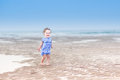 Beautiful laughing toddler girl in blue dress at beach a running a tropical Royalty Free Stock Photo